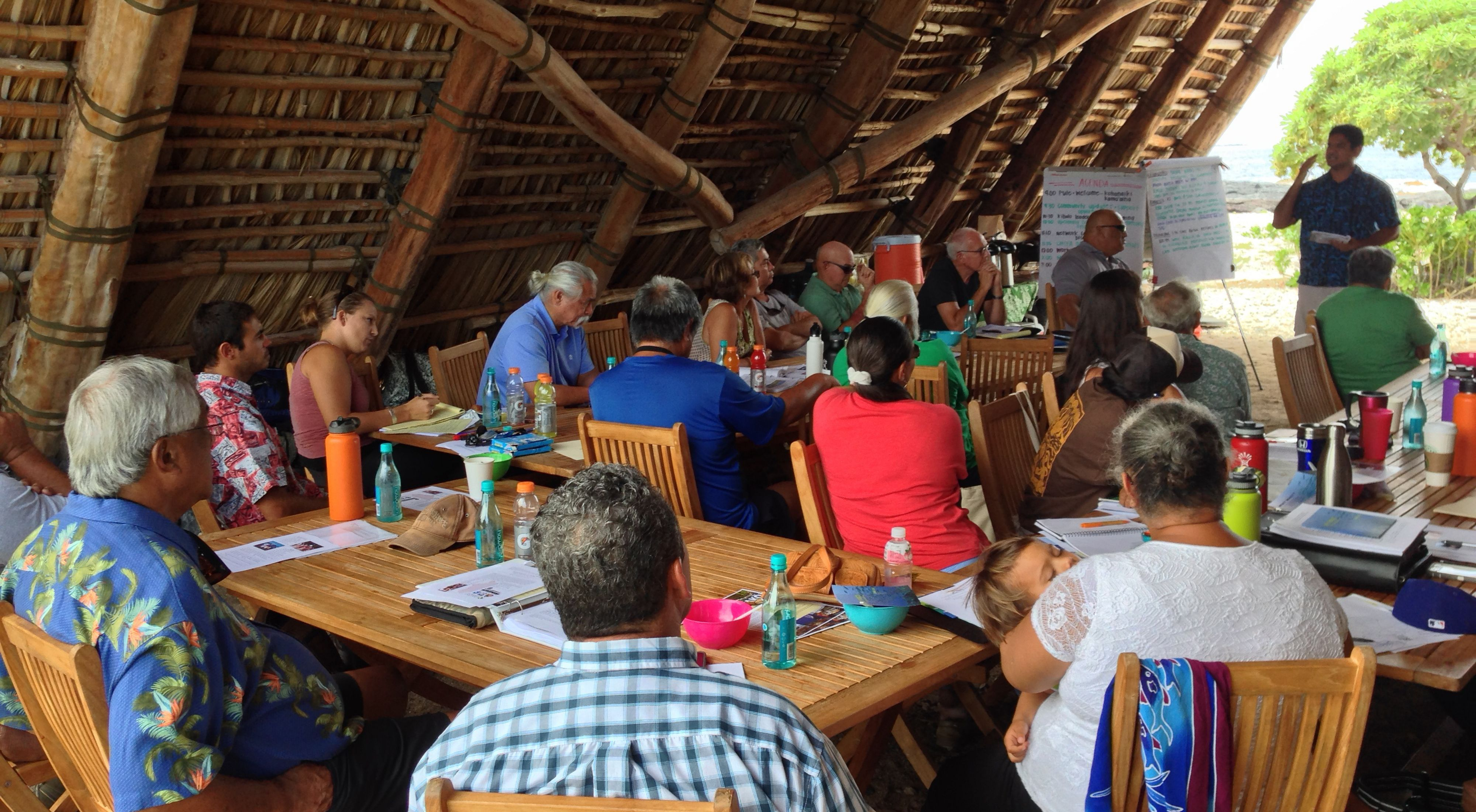 About 20 community members of all ages sitting at tables under a wooden beachside shelter listening to a presentation by a man at the front of the group.