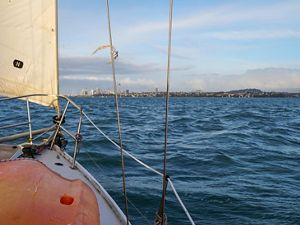 View of bay from aboard sailboat with city skyline in background.