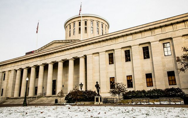 The front of the Ohio statehouse building with tall stone columns, steps leading up to the doors.