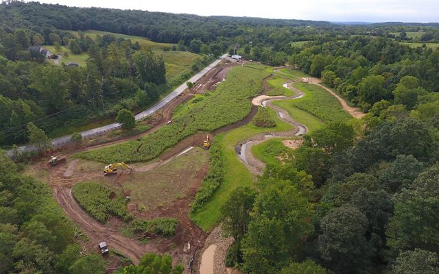 A bird's eye view of construction equipment moving dirt and recreating a winding stream among a lush forest.