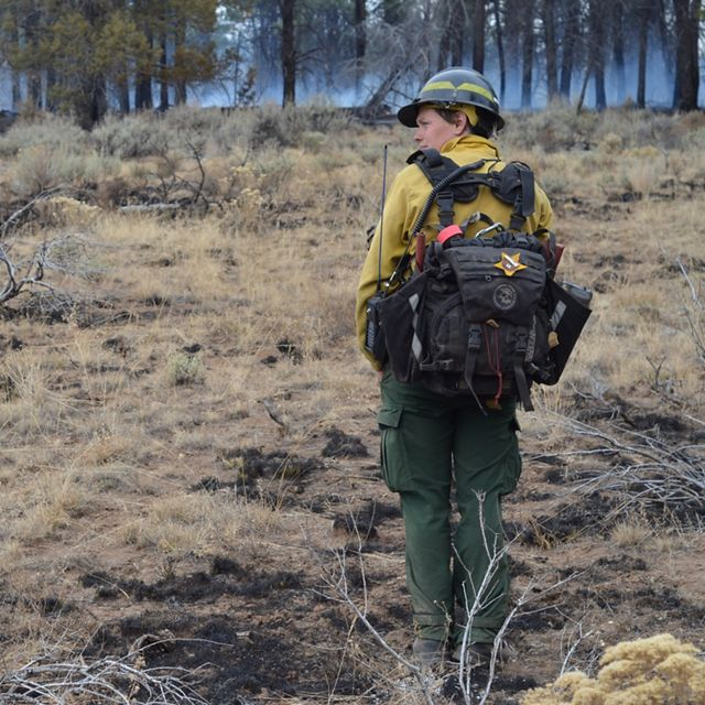 TNC Oregon Fire Manager Katie Sauerbrey stands in fire practitioner gear in front of a forest