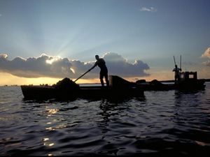 silhouette of a person on a small boat