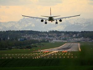 an airplane approaches a runway to land