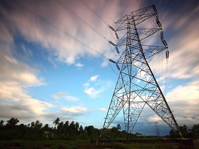 A high voltage overhead power line stands against the blue sky.
