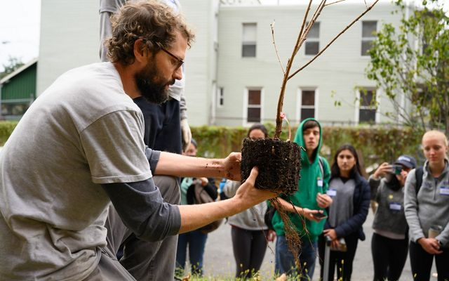 A man kneels on the ground while holding the root ball of a small sapling. A group of students watch him in the background.