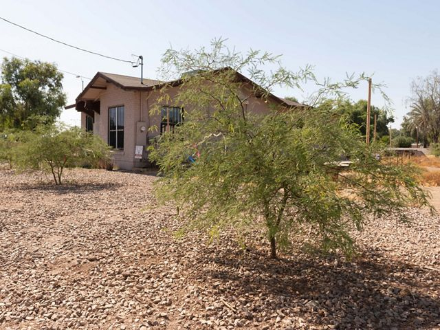 After: the same house with new trees and gravel.