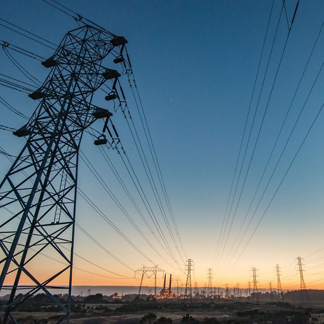 A photo of electrical transmission lines to the horizon at sunset.