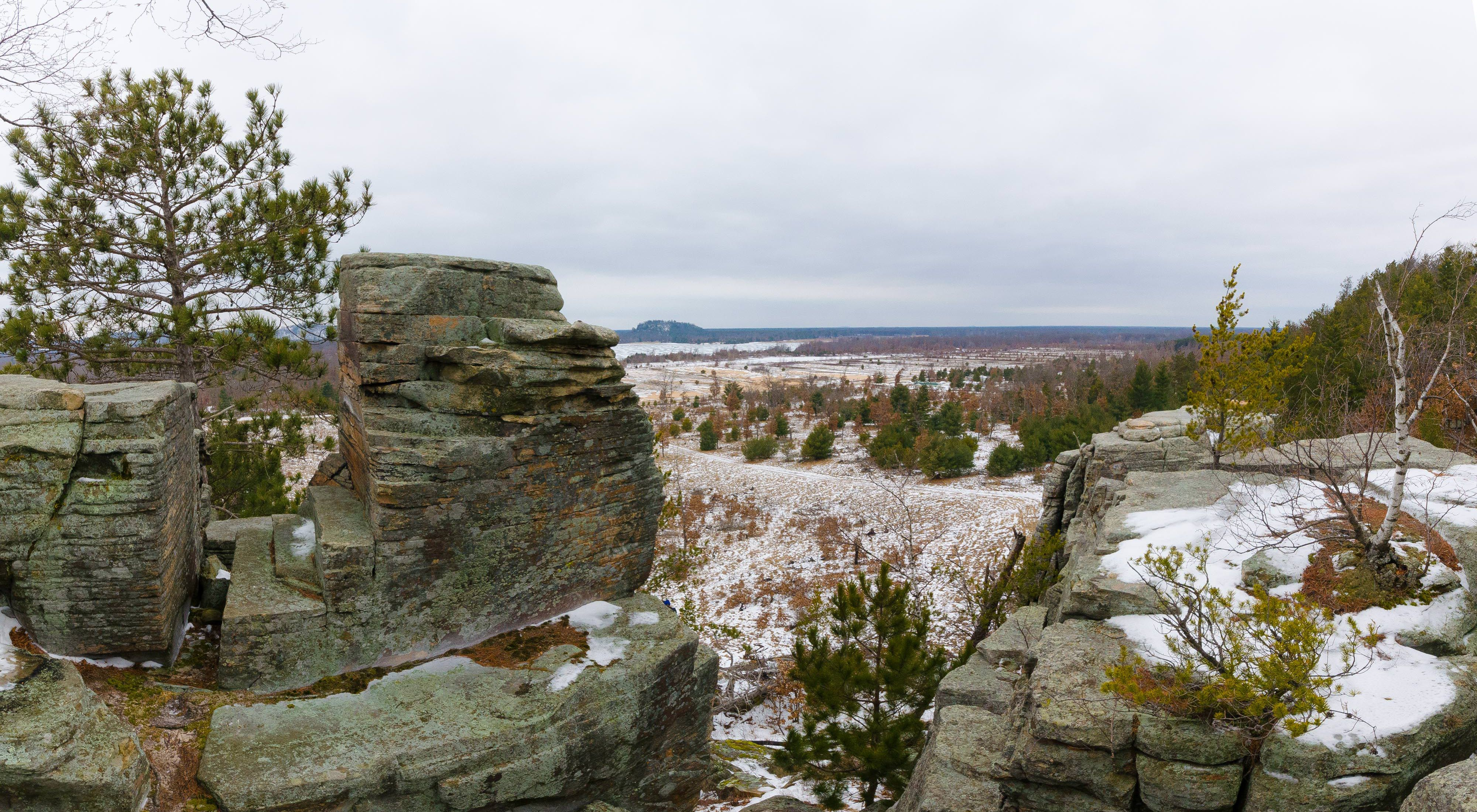 Panoramic view over the wintry landscape from the rocky, snow-covered bluffs dotted with birch and conifer trees at the Quincy Buff and Wetlands State Natural Area.
