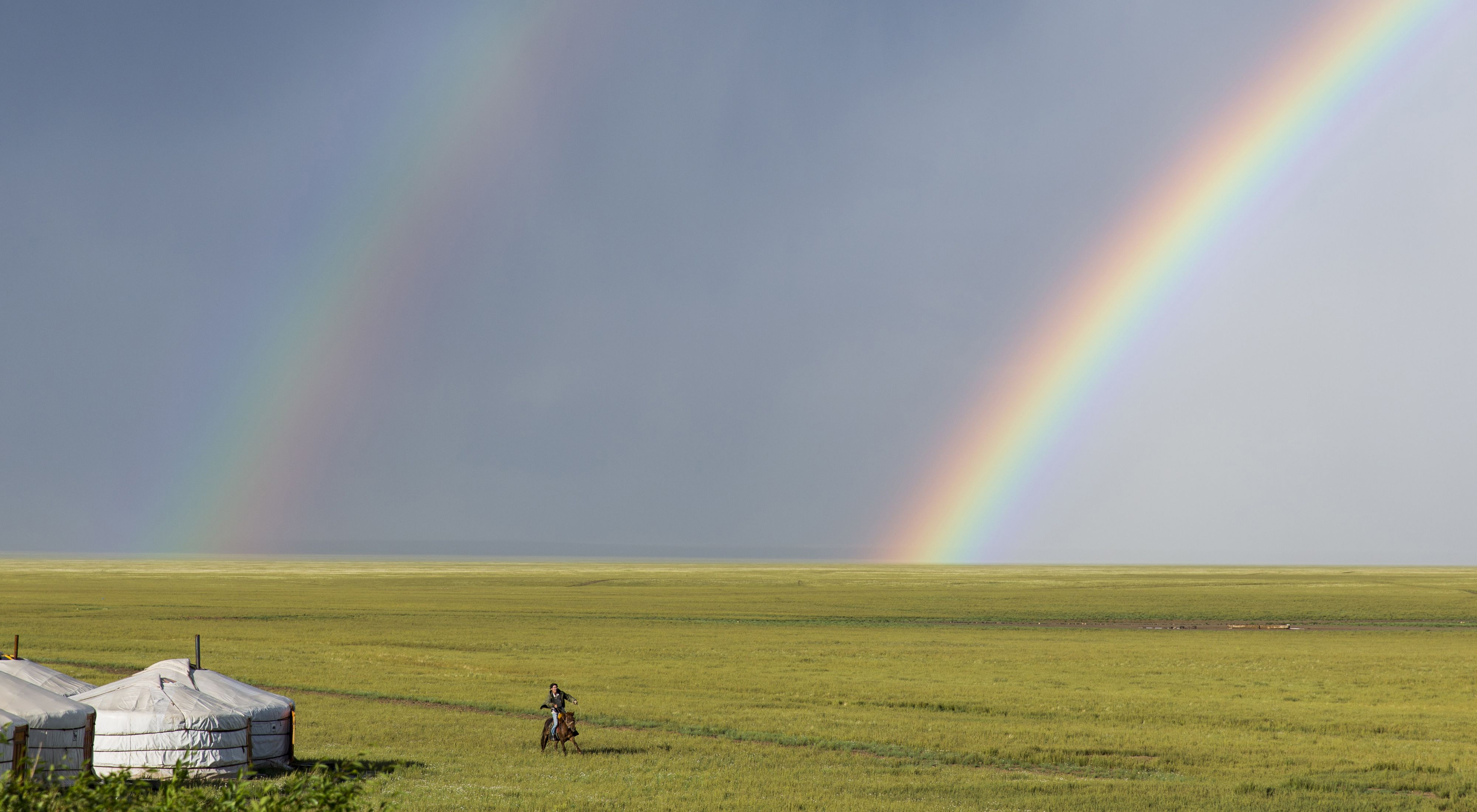 A person riding a horse past gers and a double rainbow in the South Gobi Desert, Mongolia.