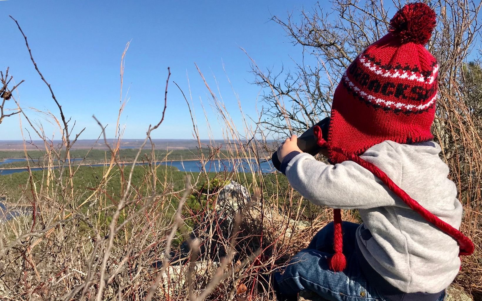 A toddler in a winter hat looks out through binoculars at the view from Rattlesnake Ridge.