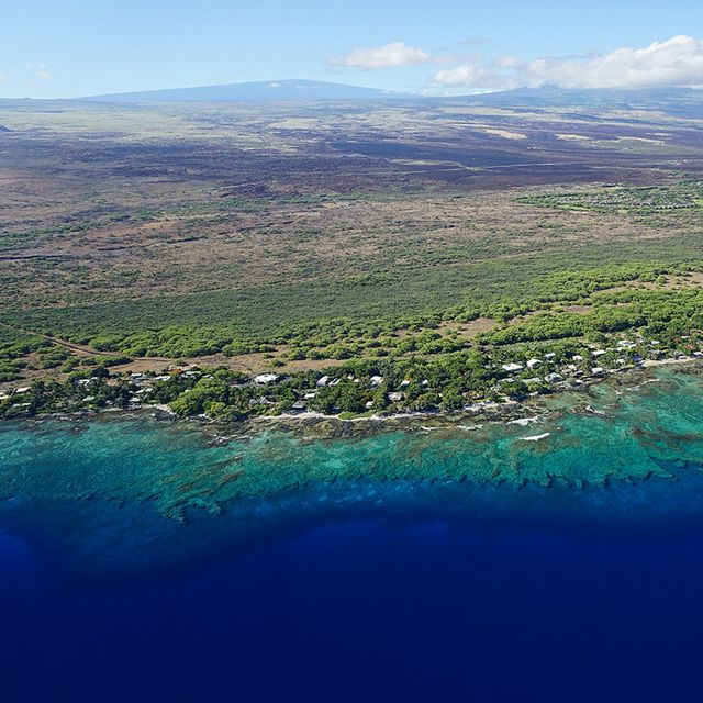 Aerial view of a green Hawai'i coastline with coral reefs below the surface of deep blue water.