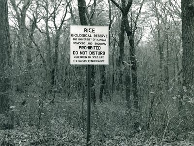 Old photograph of metal preserve sign in front of tress