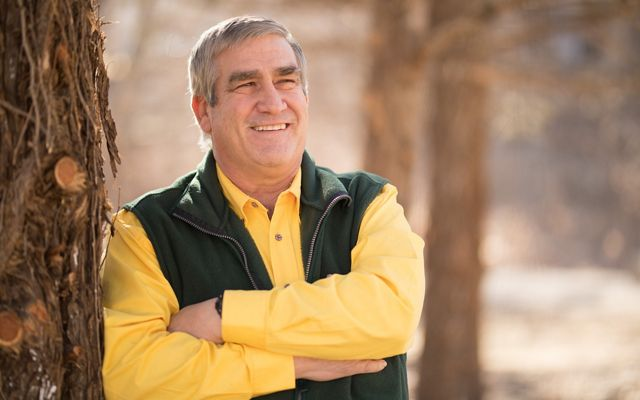 Smiling man with crossed arms leans against a tree.