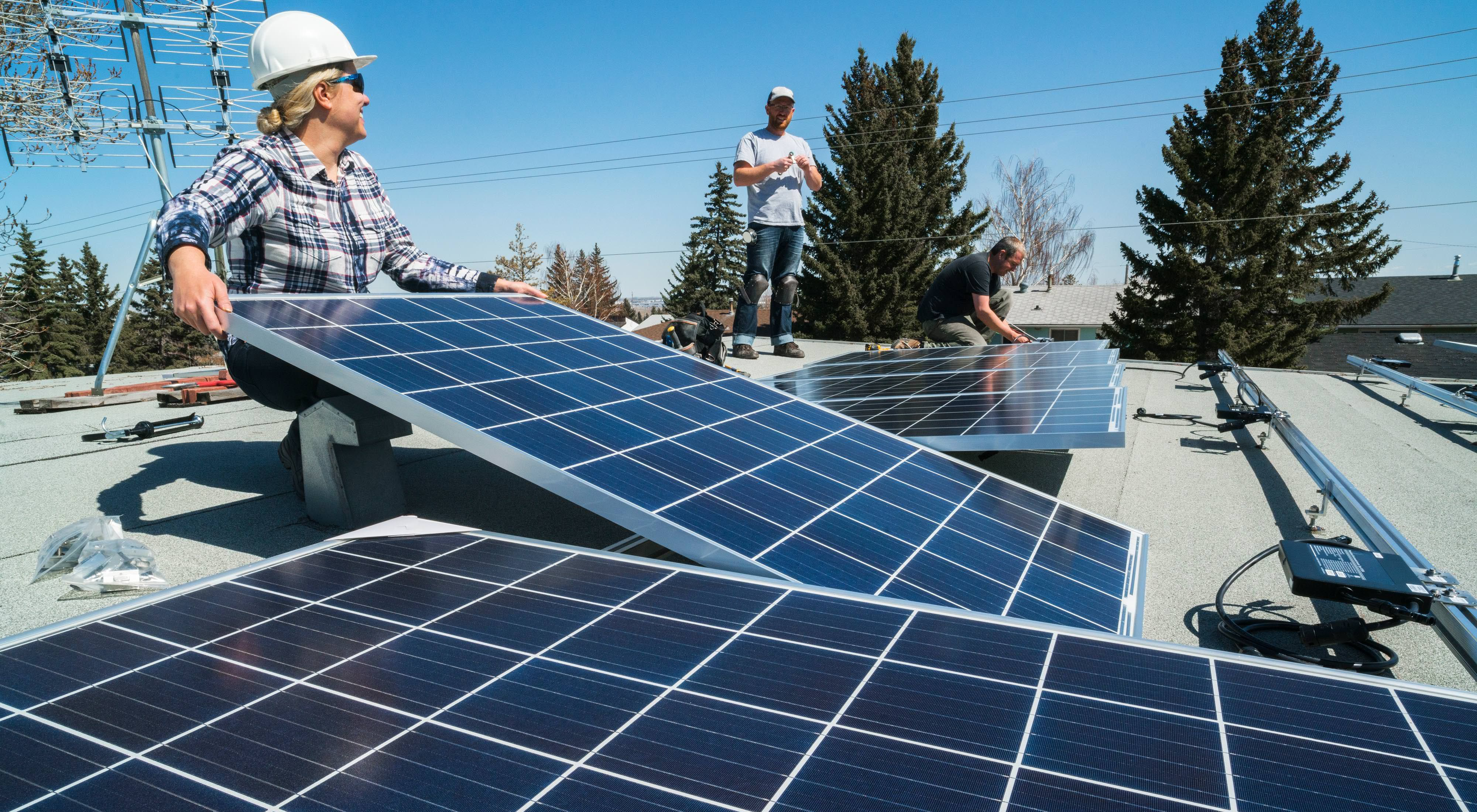 Workers installing solar panels on a residential homes roof.