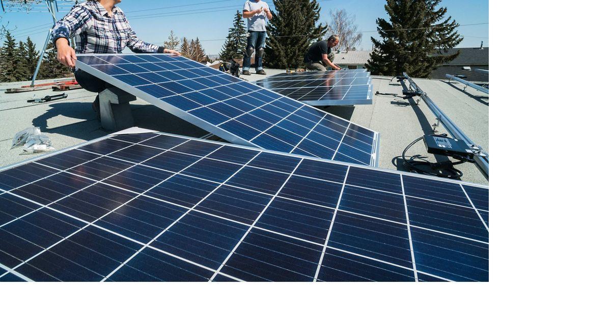 A worker installs solar panels to capture renewable energy.