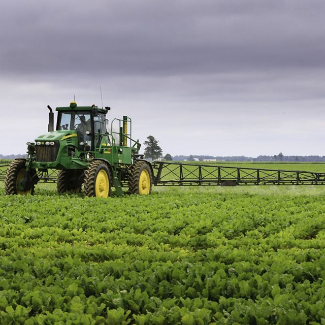 A green tractor in an agriculture field.