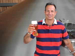 Dogfish Head Brewing holding a beer, smiling.