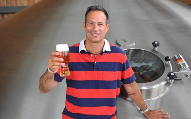 A man in a blue and red striped polo shirts holds up a glass of beer with a thick, foamy head. His other hand rests on top of  a large steel brewing tank.