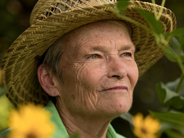 Legacy Club member Sandra Stark sits among yellow flowers with her gaze off toward the distant sky.