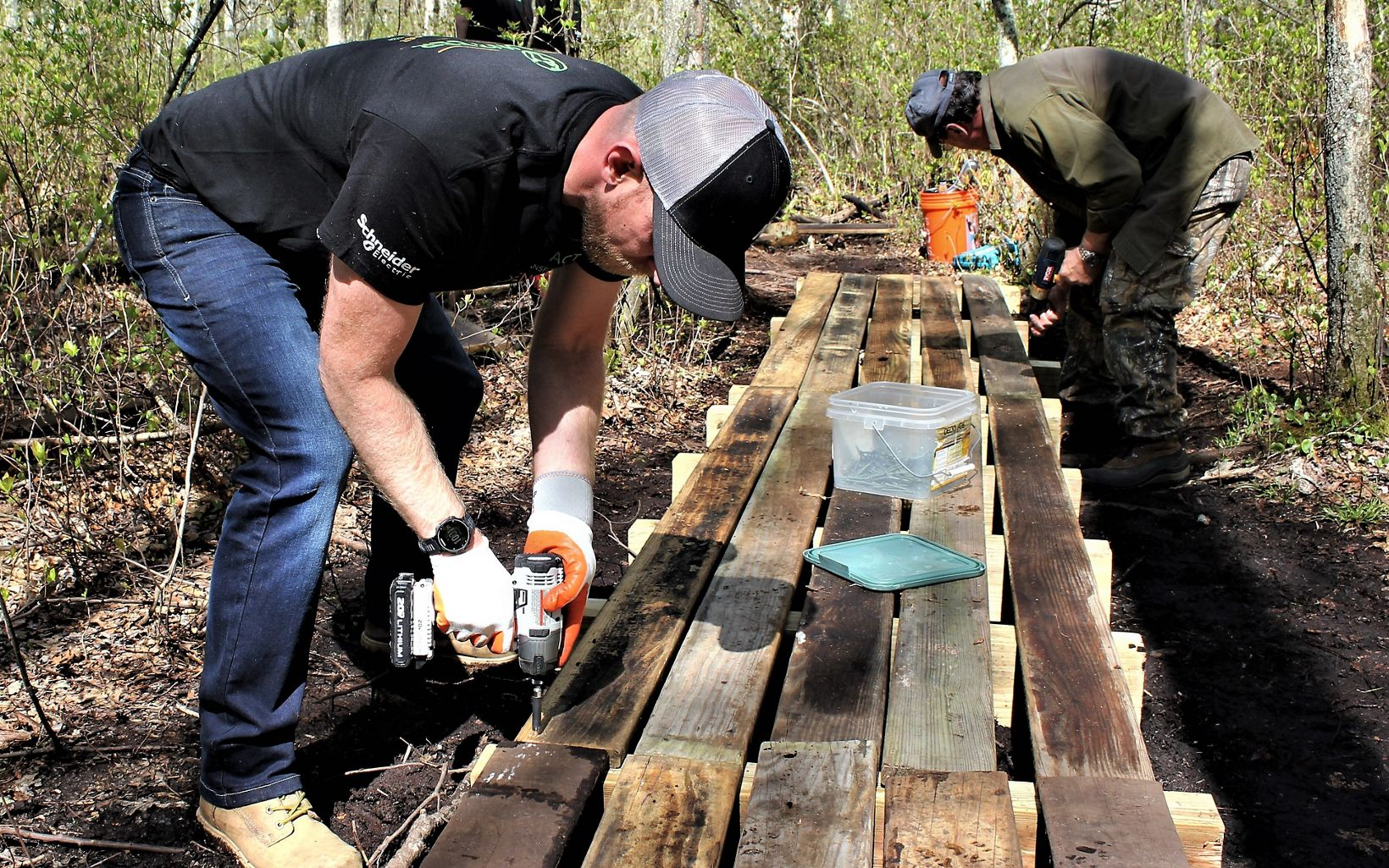 A male volunteer holding a drill crouches over a low wooden footbridge, under construction on a wooded trail.