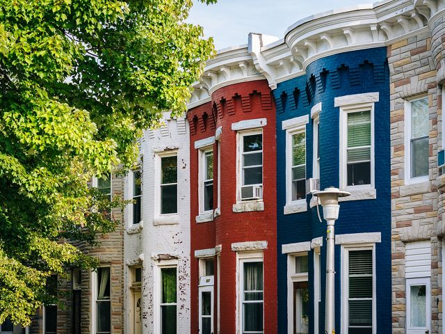 Tightly cropped view of the exterior of a street of rowhouses in Baltimore. Each house has a curving bay front. They are painted in different colors, red, white and blue.