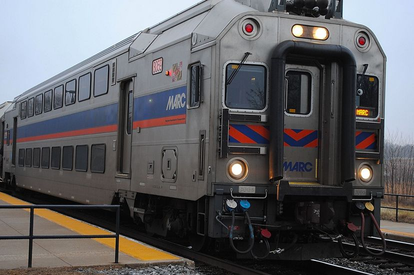 Close view of a MARC commuter train. A long silver train car with a blue and red stripe running hozirontally along the side of the car. The train is sitting at a platform.