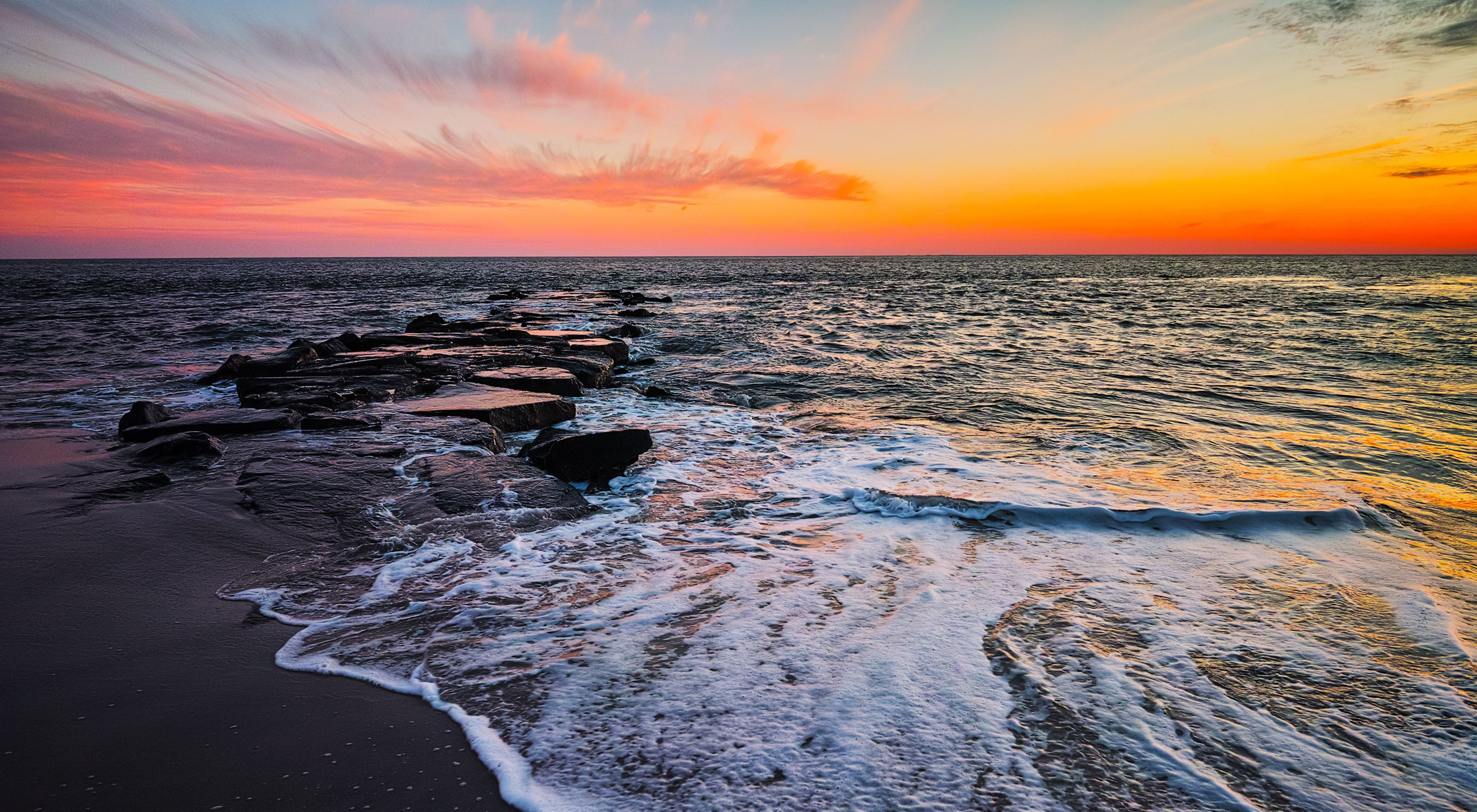 The sun is setting over a beach with waves breaking on the sand and rocks.