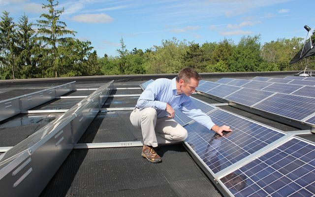 A man is kneeling by a row of solar panels on a rooftop.