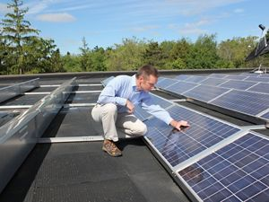 A man crouches to inspect an array of solar panels.