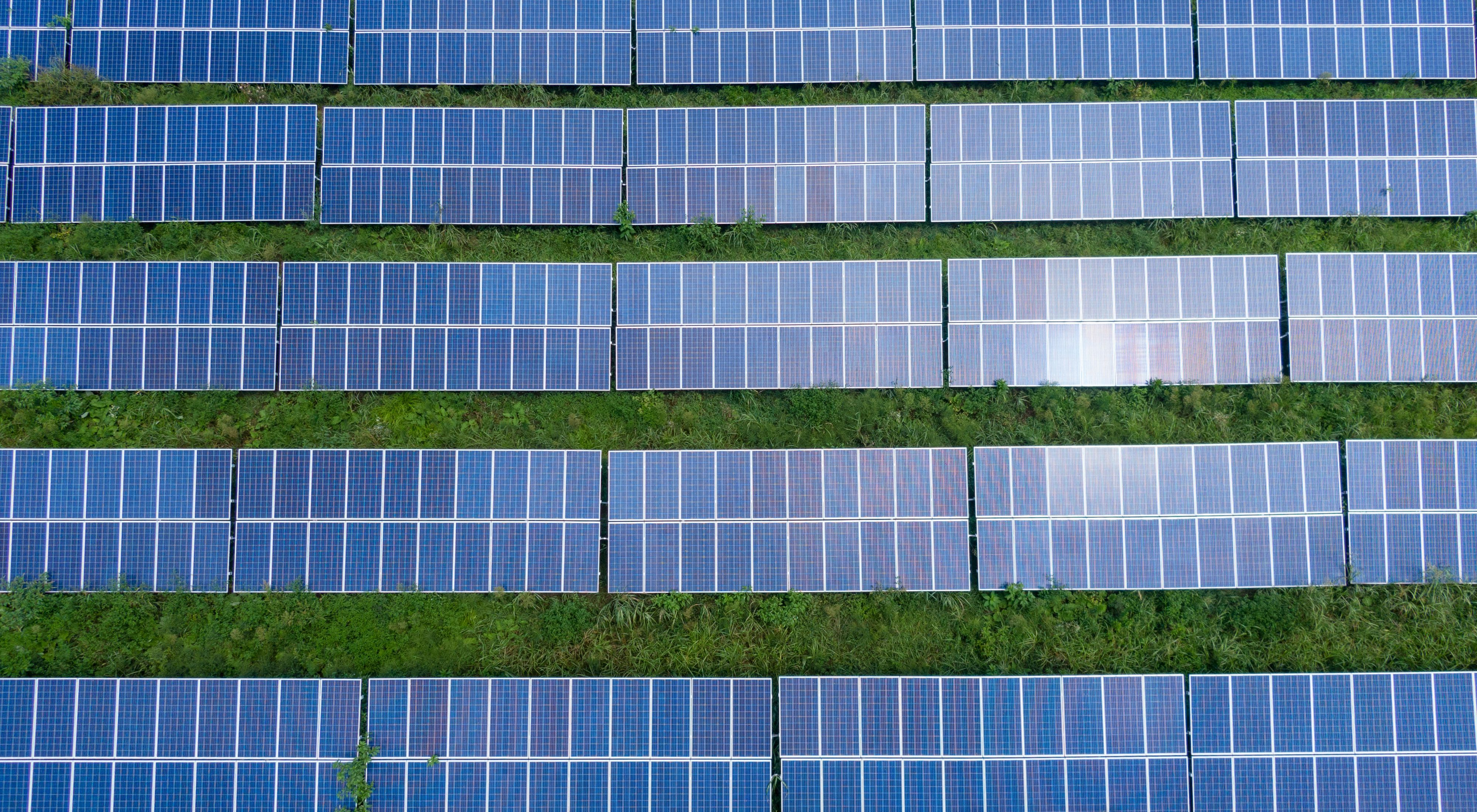 Aerial view of a row of five solar power arrays sitting atop a green grass field.
