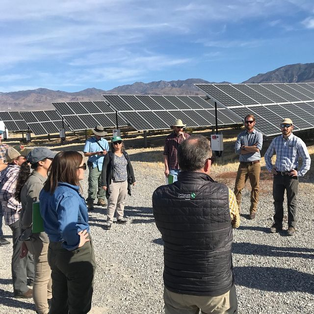 Group of people in discussion beside Nevada solar array
