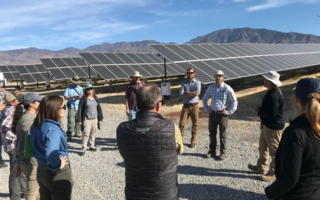 Group of people in discussion beside a Nevada solar array.
