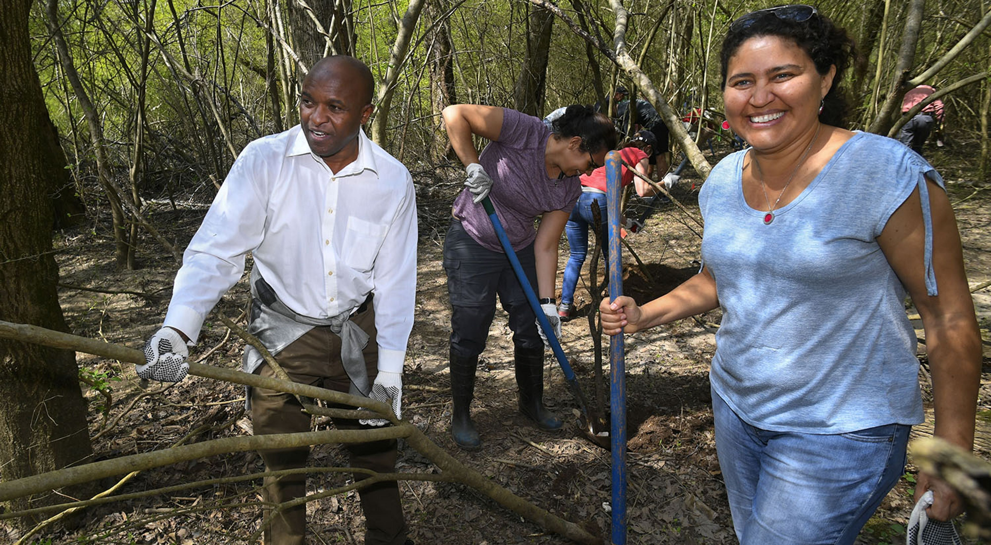 Smiling volunteers with shovels in a wooded area of the South River watershed.