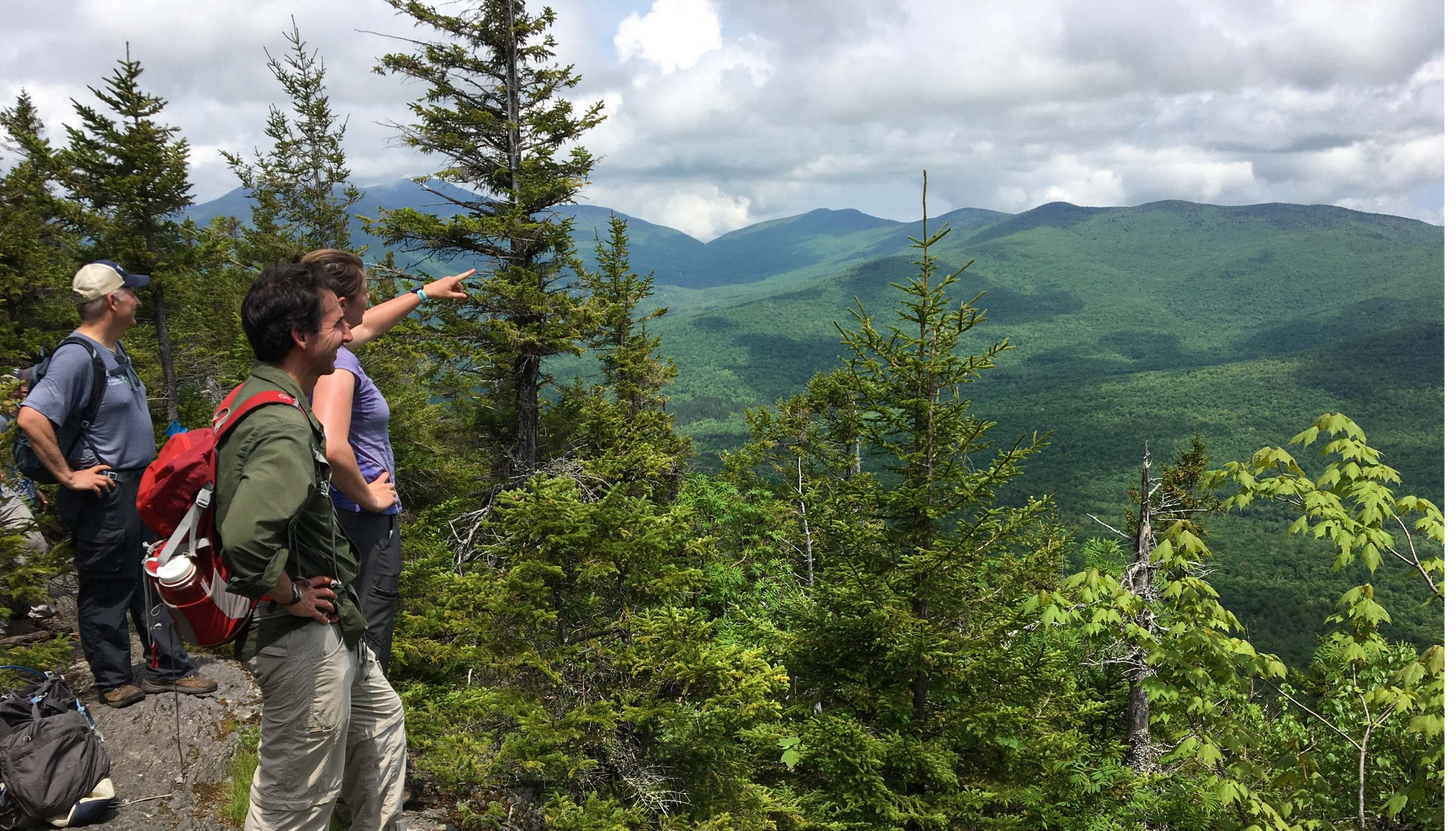 Three people standing atop Burnt Mountain in Vermont.