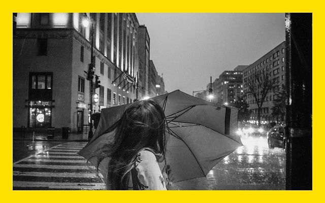 Black and white photo of a person holding an umbrella against a dark and rainy city street.