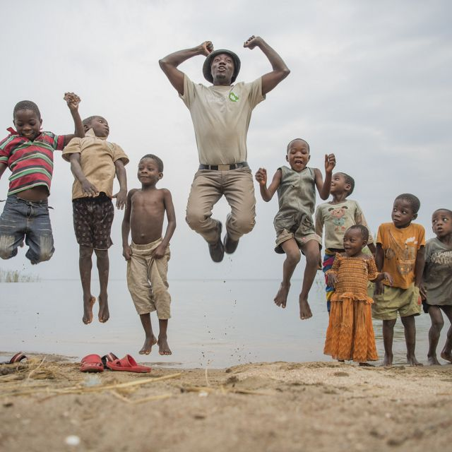 The Nature Conservancy's Peter Limbu plays with children next to Lake Tanganyika, Tanzania.