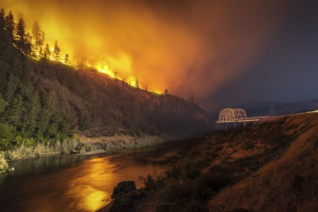 Photo of wildfire at night burning near Rogue River and Hellgate Bridge in Oregon.