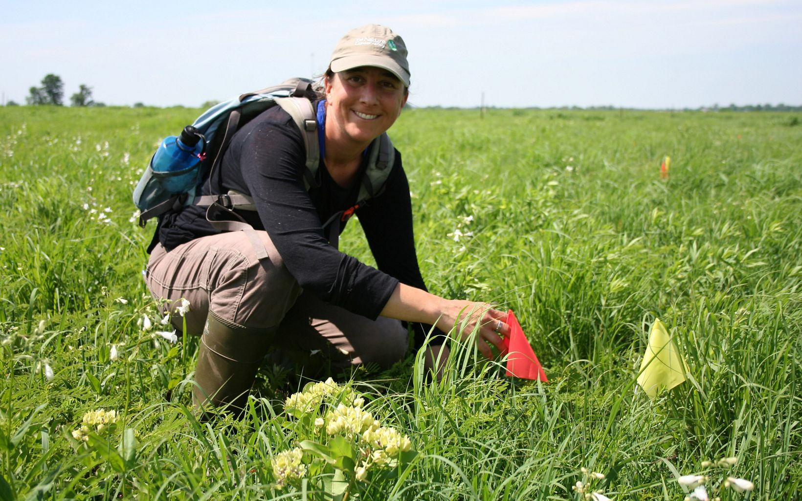 Theo Michaels, University of Kansas doctoral student, checks the condition of plants placed at Anderson County Prairies.