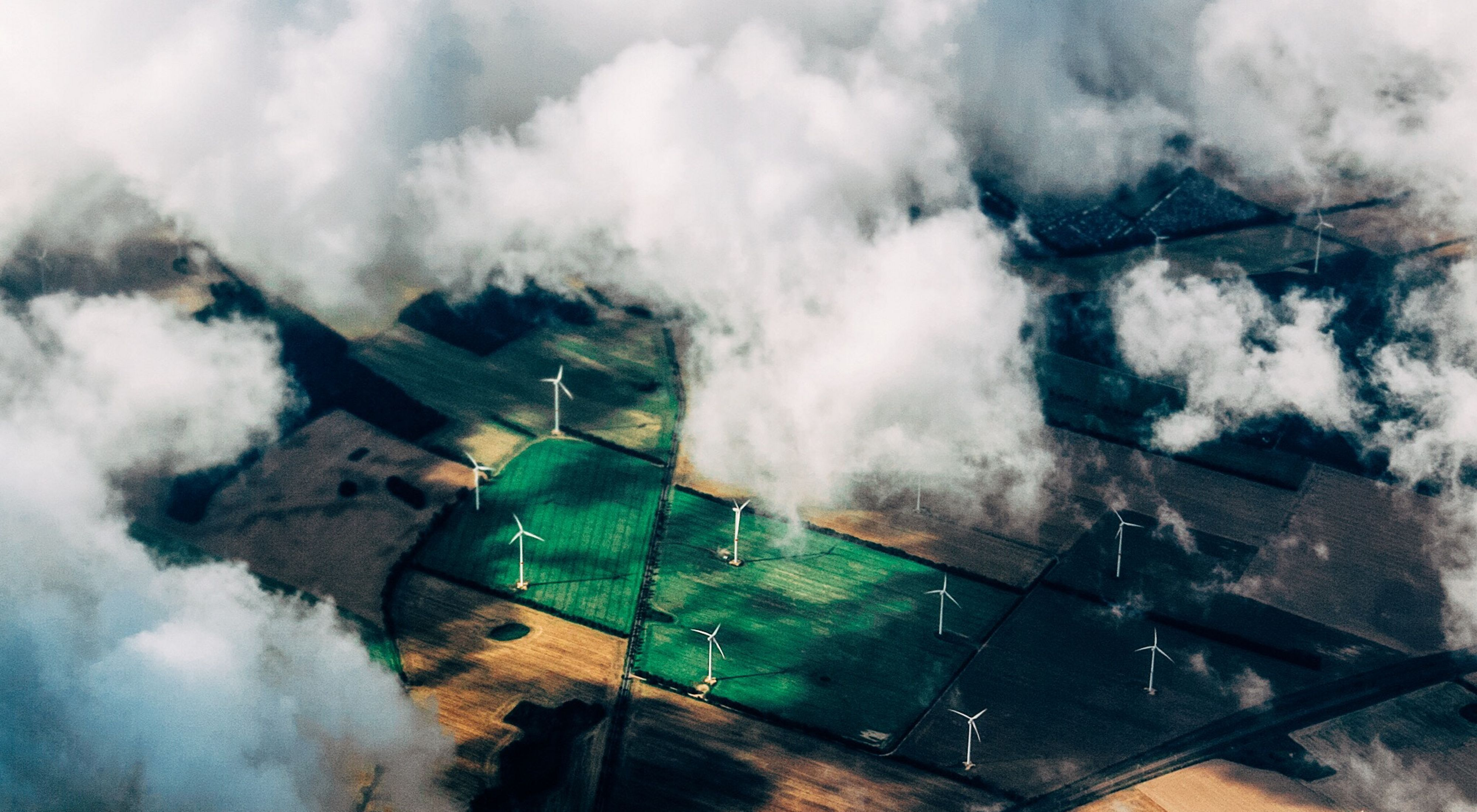 Aerial view of wind turbines on agricultural land.