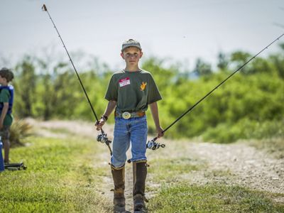 Boy holding a fishing pole in each hand looks at camera