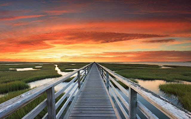 An October evening at the Bass Hole boardwalk that crosses the Chase Garden Creek Marsh in Yarmouthport, Massachusetts.