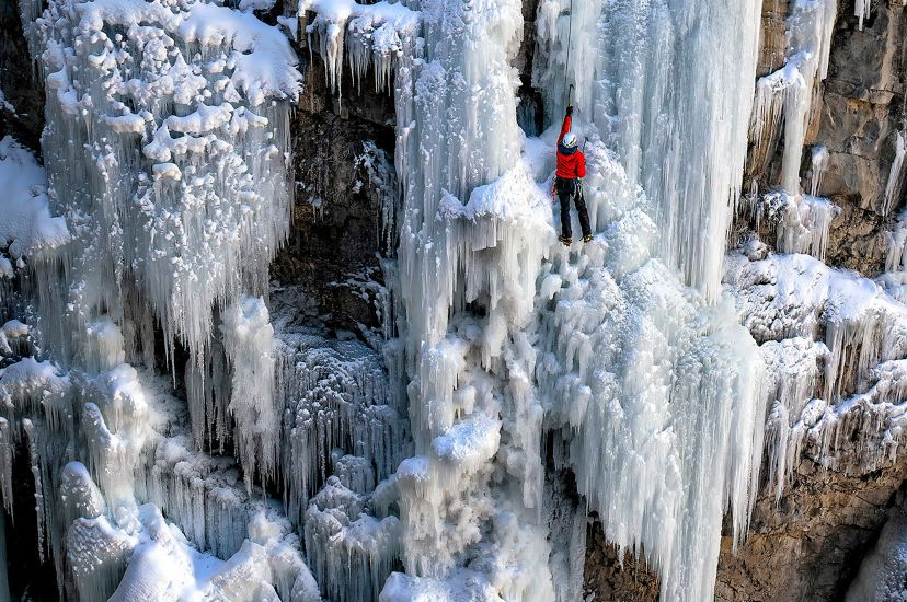 Hiker climbing frozen waterfall