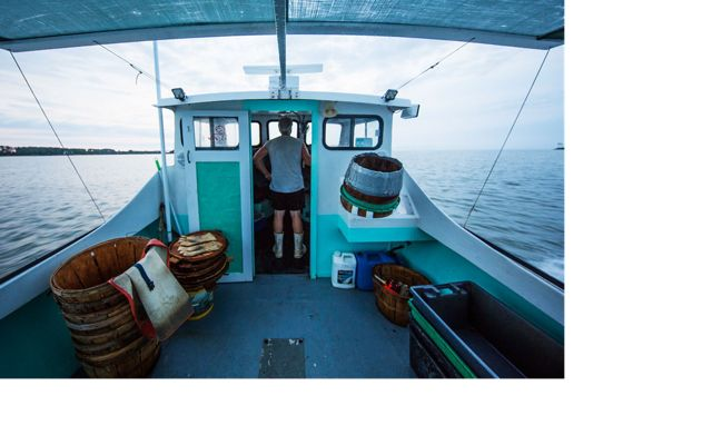 Man standing in the wheelhouse of a small boat