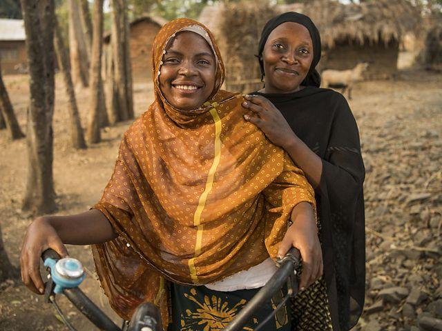 Two women stand next to bike