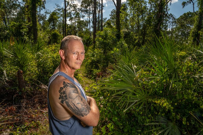 Florida man with tank top showing off florida panther tattoo on his arm while standing in a florida forest