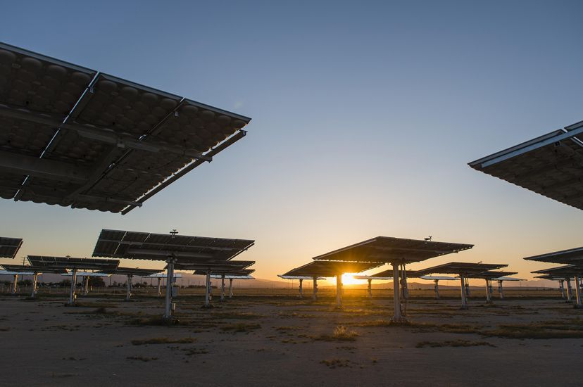 Photo of solar panels in the desert, as sun sets in background.