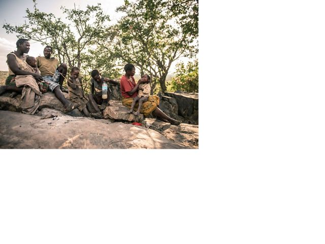Moshi Nakunda's family sits on boulders in the shade