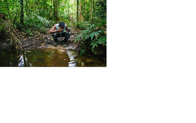 A man stops for a drink of water from a stream in the B