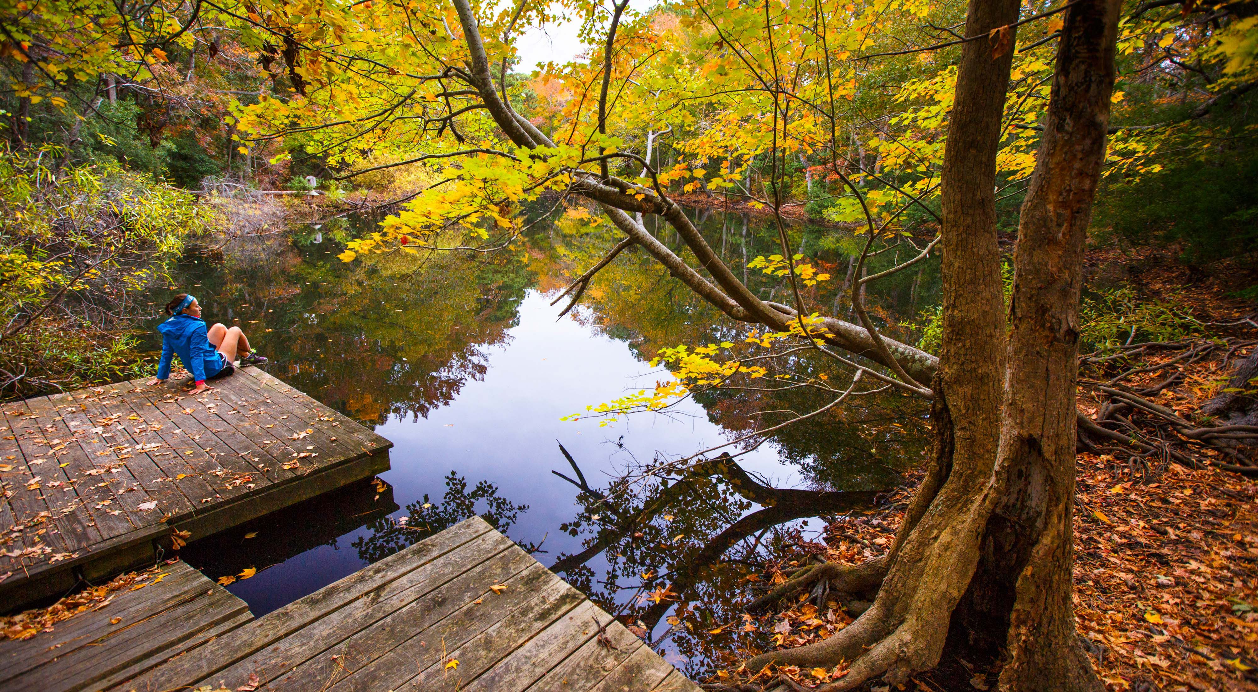 A young woman sits on a pier overlooking a pond, surrounded by trees with fall foliage.