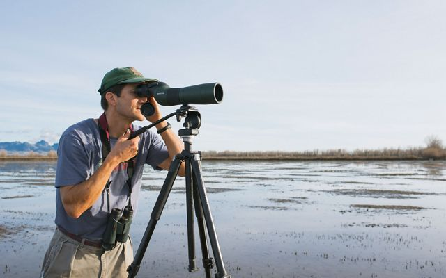 A man standing in a flooded farm field looking through a large spotting scope.